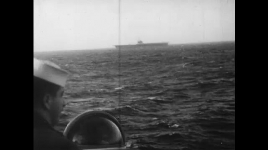 UNITED STATES: 1960S: men look out at ship on ocean. Submarine in sea.