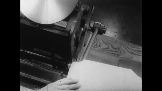 1950s: UNITED STATES: man creases along paper fold. Man inserts press board into press.