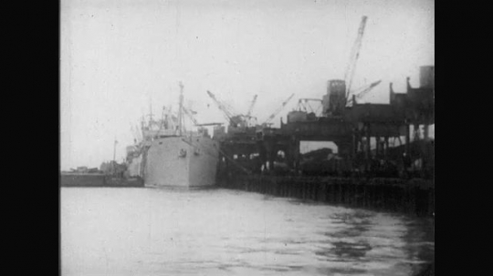 UNITED STATES: 1910s: ship in harbour. Men leave ship with kit. Trains on harbour.