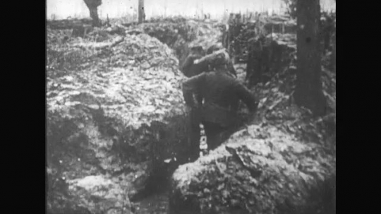 UNITED STATES: 1910s: soldiers walk through flooded trench. Men dig mud in trench. Men rest in trench. Man sleeps in trench