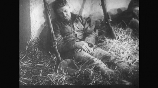 UNITED STATES: 1910s: men rest and sleep on hay in trench. Soldiers walk through trench. Men smoke cigarettes. Men watch from trench.