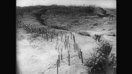 UNITED STATES: 1910s: view across trenches. Soldiers guard from trench. Barbed wire around trench. Guns fire from trench