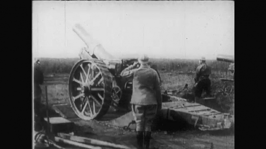 UNITED STATES: 1910s: guns roll back and forth. Guns fire from trench. Soldiers run. Man throws grenade.