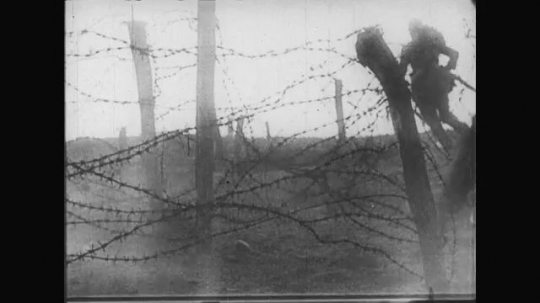 UNITED STATES: 1910s: barbed wire fence. Men fall as gun fire hits. Soldiers fire guns. Soldiers run. Soldiers fire from trench. Soldier dies after hit