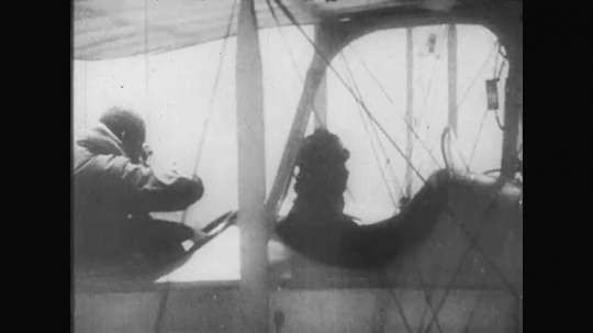UNITED STATES: 1910s: pilot in military plane in sky. Gunner in plane. Gunner fires weapons.  at planes. Plane takes hit. Plane falls to ground.