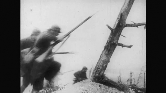 UNITED STATES: 1910s: soldiers run past tree. Soldiers hit and collapses. Soldier fires bullets.