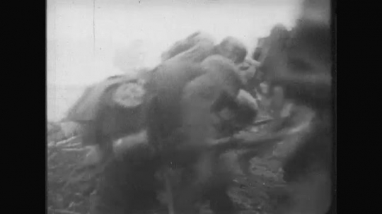 UNITED STATES: 1910s: soldiers run across ground. Soldiers step over bodies. Soldiers jump into trench.