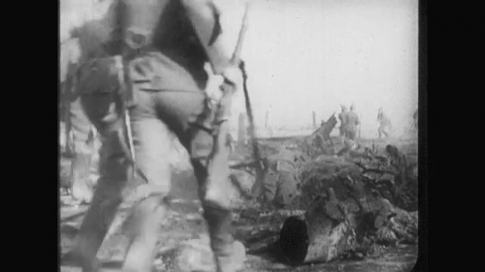 UNITED STATES: 1910s: soldiers run across ground. Soldiers step over bodies. Soldiers jump into trench. View from above.