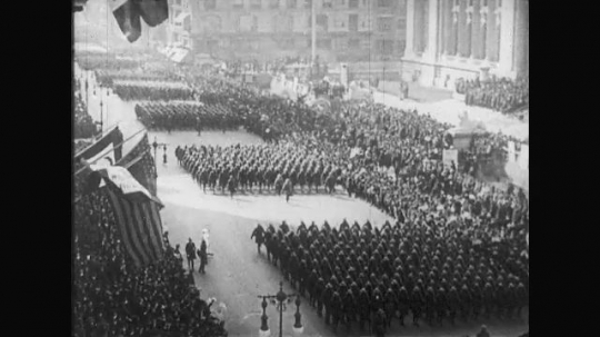 UNITED STATES: 1910s: soldiers march through streets. Crowds watch as soldiers arrive home. Officer salutes.