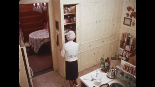 UNITED STATES: 1970s: elderly lady makes toast in kitchen. Lady makes cup of tea.