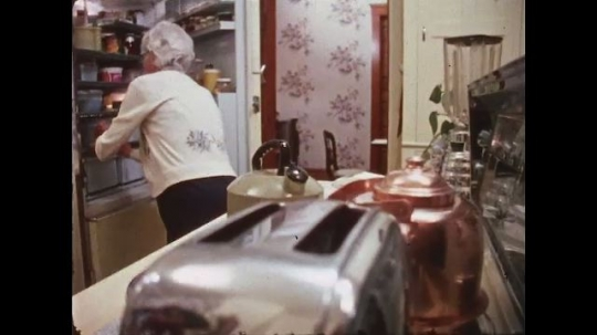 UNITED STATES: 1970s: toast in toaster. Lady makes tea in kitchen.