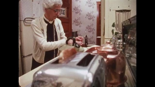 UNITED STATES: 1970s: lady puts lid on pot. Lady prepares food in kitchen. Lady takes toast from toaster.