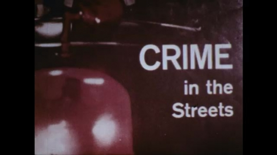 UNITED STATES: 1970s: poster for crime in streets. Lady goes into house at night. Close up as door closes.