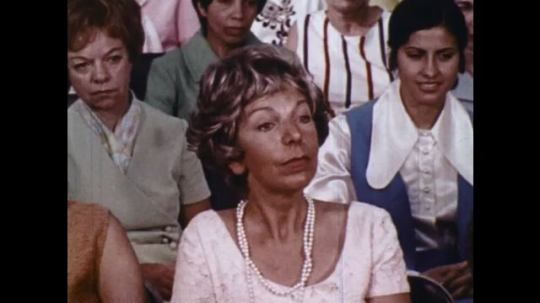 UNITED STATES: 1970s: lady in audience. Man speaks to audience.