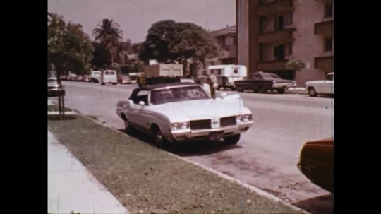 UNITED STATES: 1970s: lady gets out of car. Lady carries shopping on pavement. Chief of Police speaks to ladies in meeting