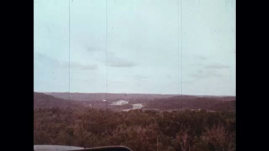 UNITED STATES: 1970s: man flies helicopter over forest. View across forest floor