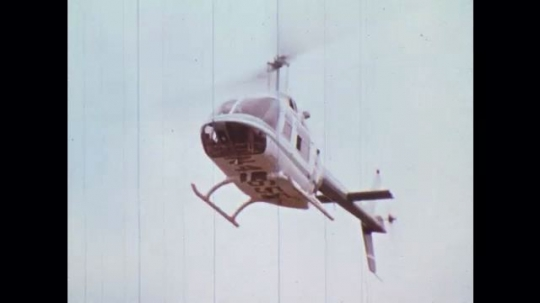 UNITED STATES: 1970s: helicopter in sky. Boy on track. Helicopter lands by boy. Man gets out of helicopter.