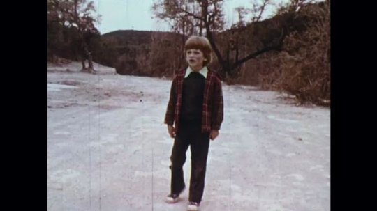 UNITED STATES: 1970s: man finds boy. Man picks up lost boy. Sheriff by car. Helicopter on ground