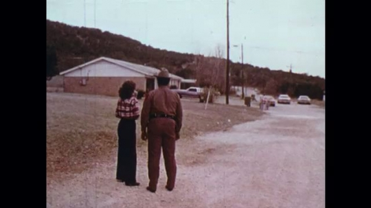 UNITED STATES: 1970s: lady with sheriff. Police car arrives with lost boy. Boy hugs mum