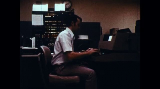 UNITED STATES: 1970s: man adds criminal record data to computer. Radiation Area sign.