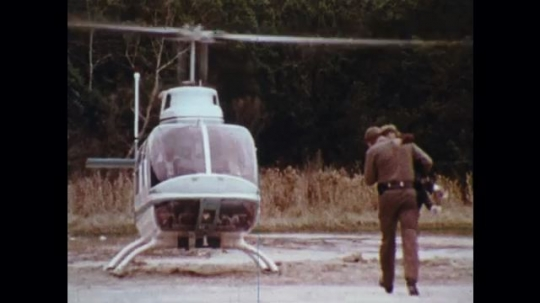 UNITED STATES: 1970s: officer carries lost boy to helicopter in woods.
