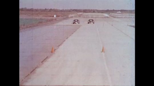 UNITED STATES: 1970s: cars drive on wet and dry surfaces in research test. View through car windscreen in rain.