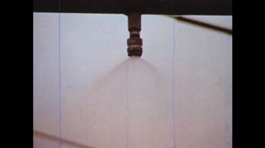 UNITED STATES: 1970s: rain maker machine on test surface. Car drives through rain on road. Surface close up of pavement