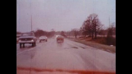 UNITED STATES: 1970s: car drives along wet road. Car research track.