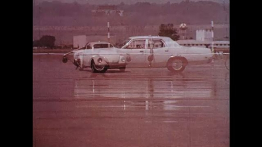 UNITED STATES: 1970s: VW car and Ford car drive along test road in wet conditions