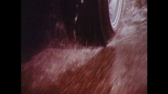 UNITED STATES: 1970s: tyres on wet road. Speed limit sign. View through car windscreen in rain.