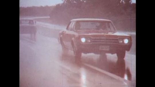 UNITED STATES: 1970s: cars on highway in rain.