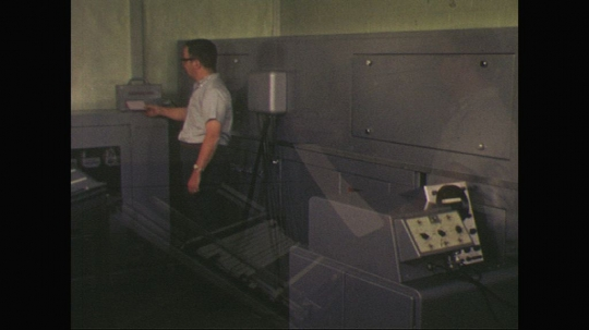 UNITED STATES: 1960s: man works with switchboard buttons. Man works with machine in room. Man tears paper from machine. Man uses edge.