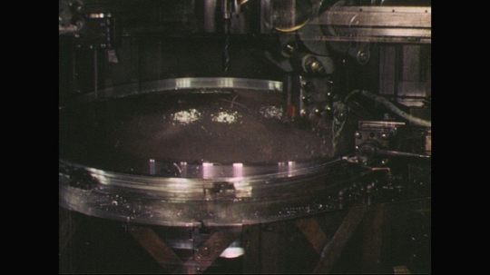 UNITED STATES: 1960s: liquid pours into round metal bowl in factory
