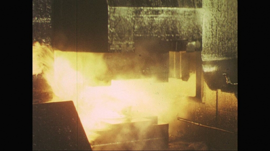 UNITED STATES: 1960s: machine presses metal into shape. Worker removes metal.