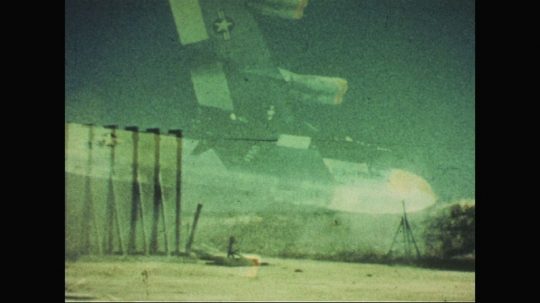 UNITED STATES: 1960s: plane in sky. Space rocket on launch pad. Falling debris as rocket launches.