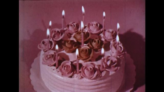 UNITED STATES: 1960s: candles on birthday cake. Still life of fruit. Colours in circles.