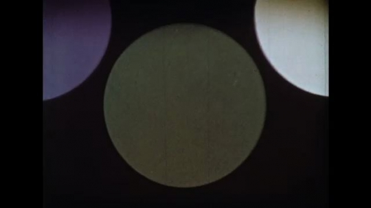 UNITED STATES: 1960s: green circle. Purple circle. Pink circle. Close up of ice.