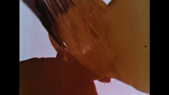 UNITED STATES: 1960s: brush mixes orange paints.  Pink and purple paints mixed with brush