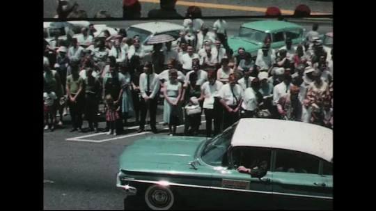 UNITED STATES: 1960s: car drives through street parade. Marching band.