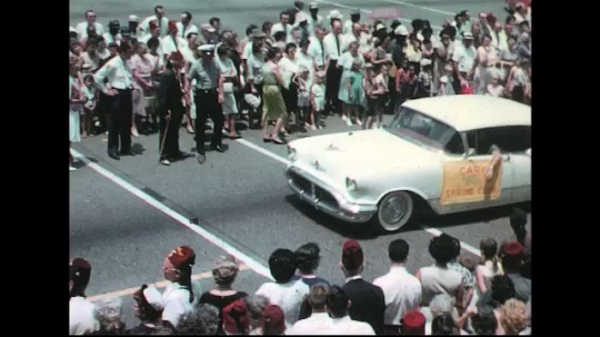 UNITED STATES: 1960s: band marches behind cars in parade. Ladies on float