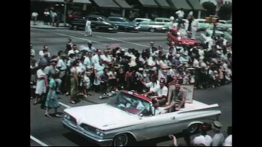 UNITED STATES: 1960s: people sit in street parade car. People in float.