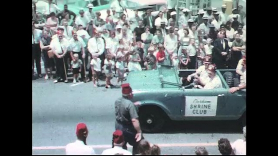 UNITED STATES: 1960s: man gets in carnival car. Tiny car in parade. Ladies wave from car