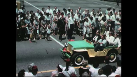 UNITED STATES: 1960s: people in car. Marching band. Van with Red Cross.