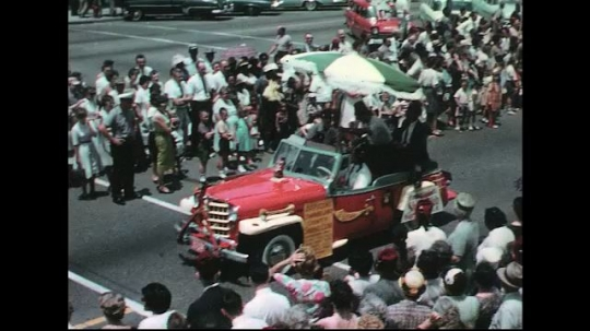 UNITED STATES: 1960s: umbrella attached to car. Vintage car in street parade.