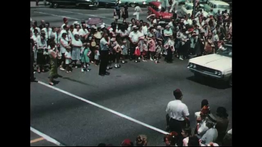 UNITED STATES: 1960s: cars in street parade. Carnival float. People marching.