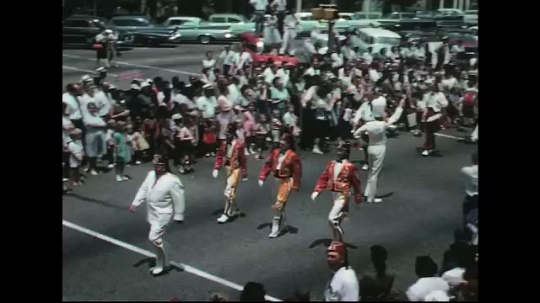 UNITED STATES: 1960s: marching band in street parade. Clown on tiny bike. Clown dances in street
