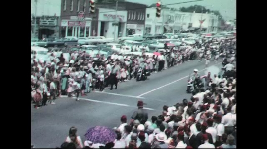 UNITED STATES: 1960s: police and clown in parade. Marching band.