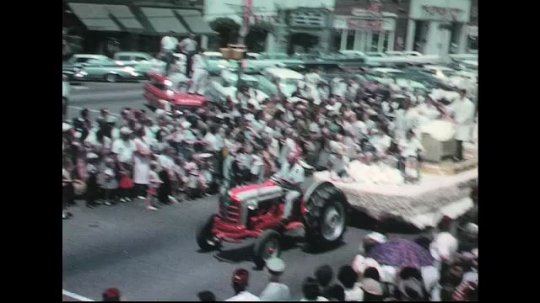 UNITED STATES: 1960s: tractor pulls carnival float. Marching band.