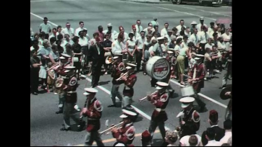 UNITED STATES: 1960s: marching band. Small car pulls float.