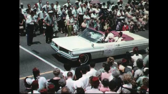 UNITED STATES: 1960s: carnival car. Ladies on float. Marching girls.